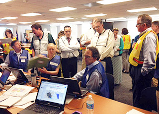 Photo of a group of NOAA employees observing data on computer screens