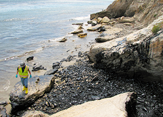 NOAA worker walking over rocks on the coastline of Refugio State Beach