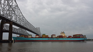 Large container ship passing under a bridge on the Mississippi River.