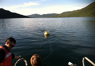 NOAA water level buoy being deployed in Terror Bay, Alaska.