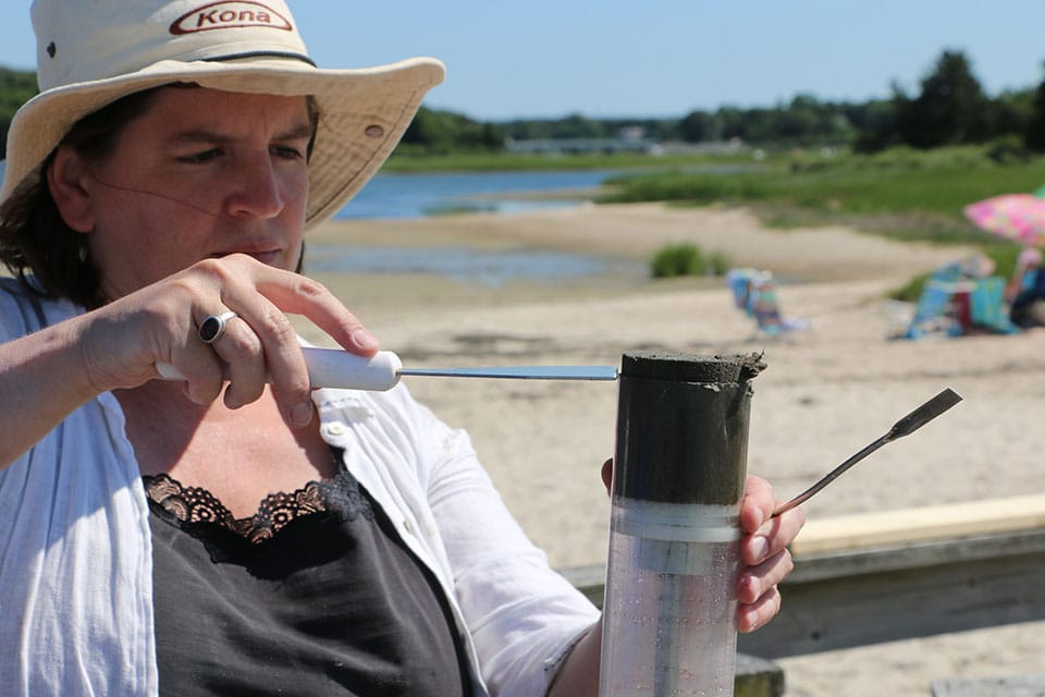 MIT Sea Grant coastal ecologist Julie Simpson takes samples from a sediment core taken inside an eelgrass bed