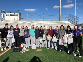 High school girls' lacrosse team collecting recyclables from athletic field.