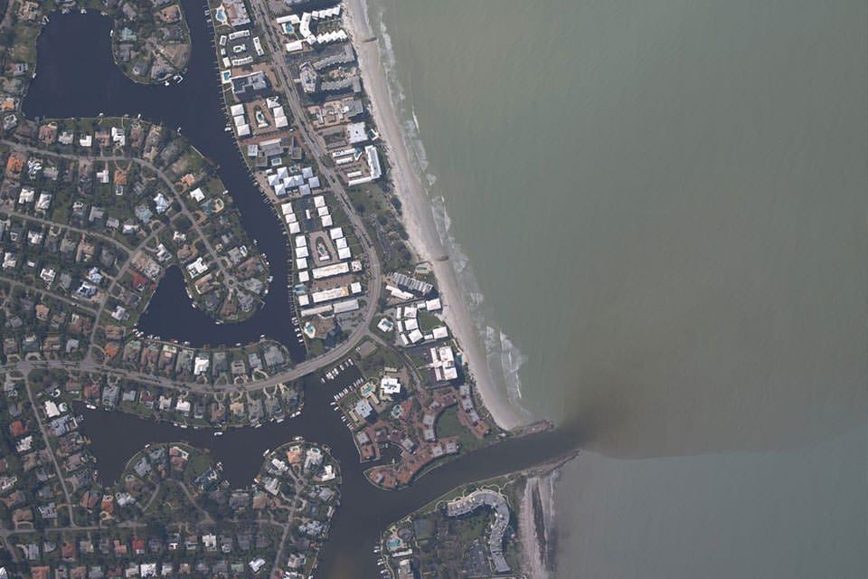 an aerial view of an estuary showing runoff in the ocean