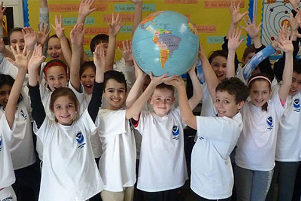 kids holding up a globe