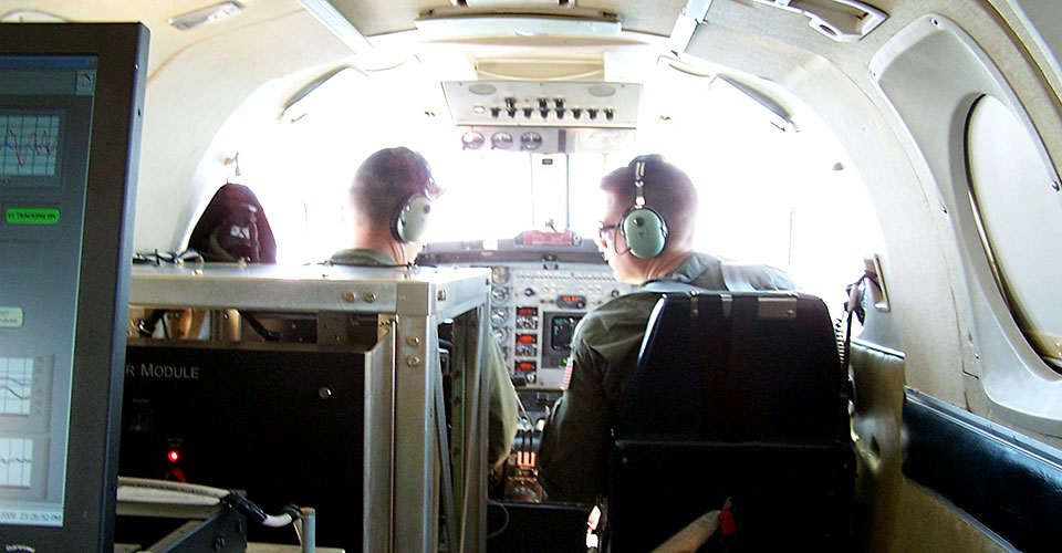 The pilot and co-pilot of a Navy-owned King Air aircraft prepare for takeoff on a data collection flight with GRAV-D instruments (fore and mid-ground) and a GRAV-D operator as their payload.