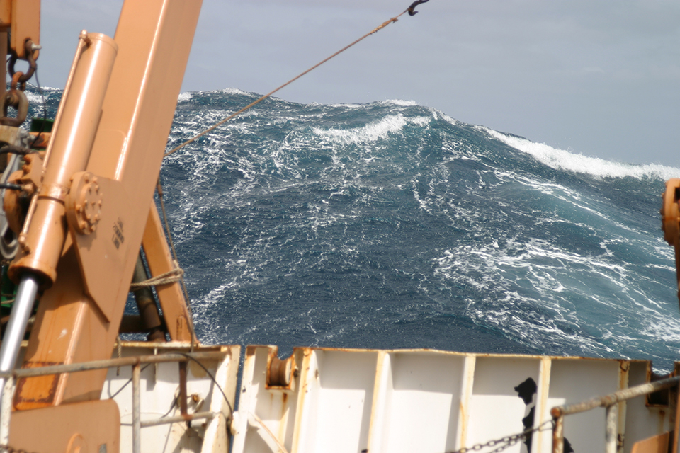 Past the rigging of a ship at sea, the ocean swells high above the horizon of the ship.