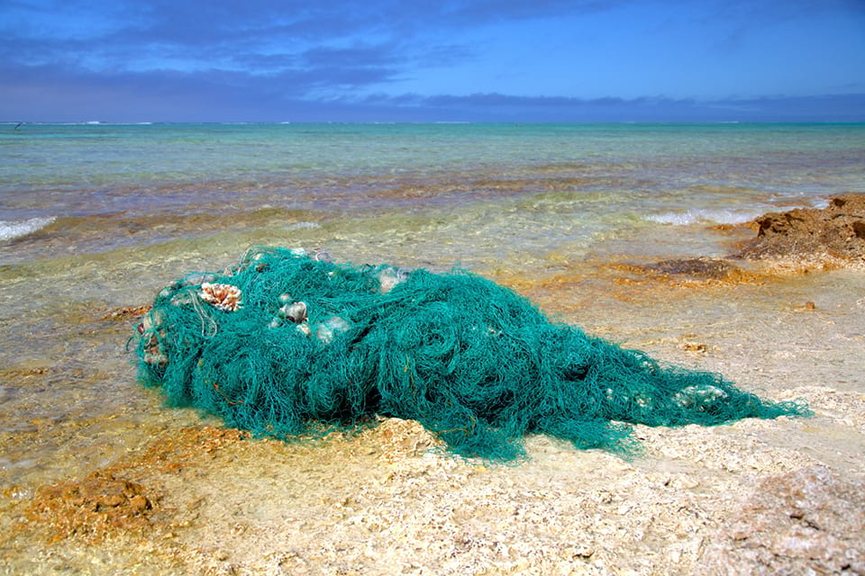 Image of a fishing net that has become marine debris bundled up on a beach