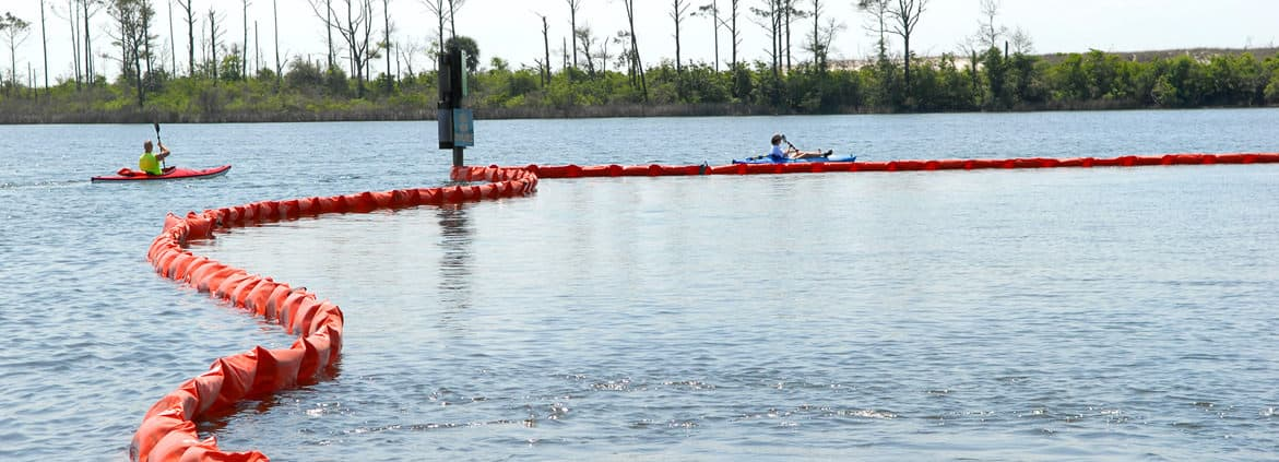 Kayakers at Naval Air Station Pensacola detour around oil containment boom on base at Sherman Cove , Pensacola, Florida, on May 4, 2010. The boom was set to protect environmentally sensitive grass beds from the Deepwater Horizon oil spill. Credit: U.S. Department of Defense