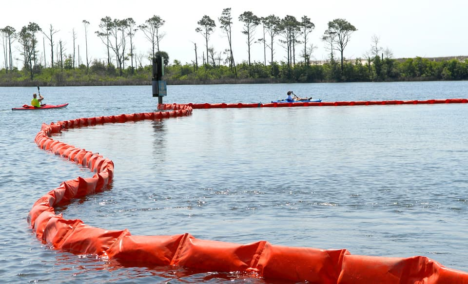 Kayakers at Naval Air Station Pensacola detour around oil containment boom on base at Sherman Cove , Pensacola, Florida, on May 4, 2010.