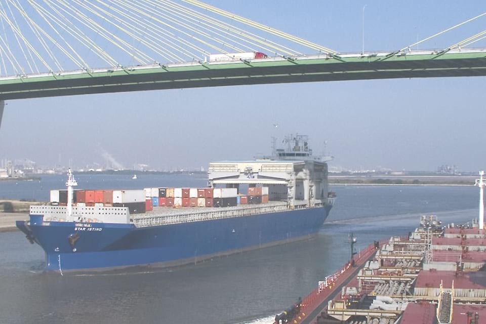 a shipping vessel going under a bridge