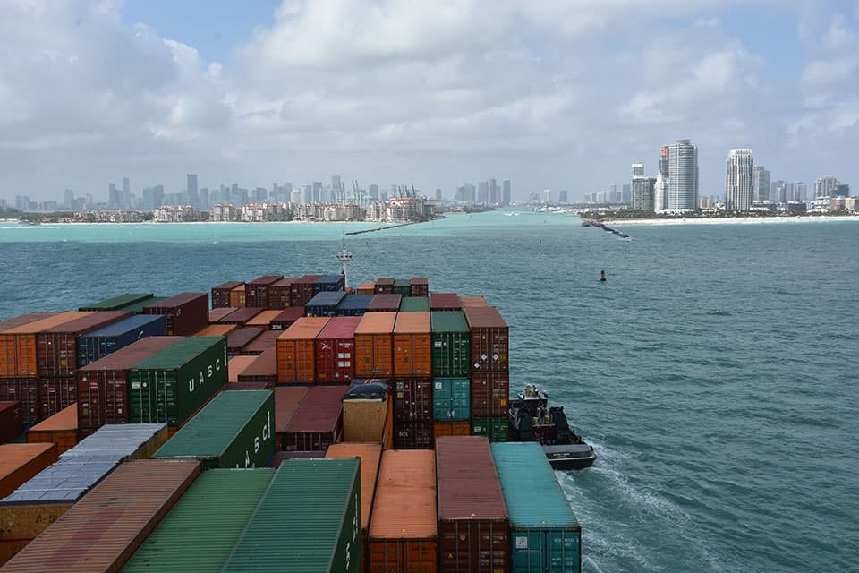 The city of Miami stands in the distance as a shipping vessel carrying multi-colored shipping containers, stacked eleven to fourteen wide and three to four high, is guided into the crystal blue waters of PortMiami by a tug boat.