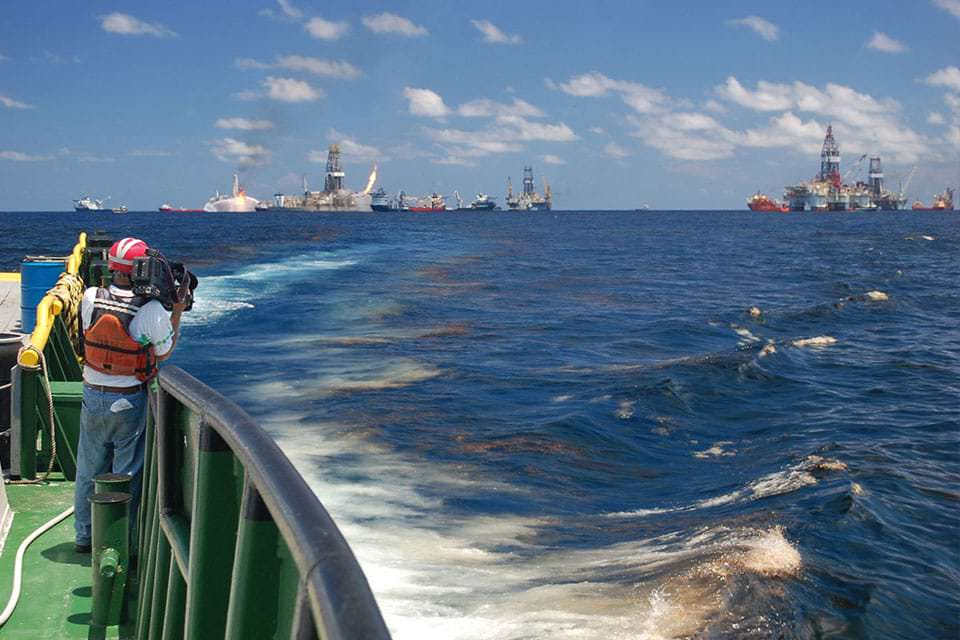National Geographic videographer Bob Perrin films an oil slick at the Deepwater Horizon site