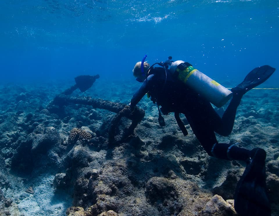 A diver examines an anchor at the Two Brothers shipwreck site.