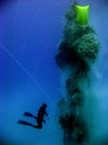 A specially trained NOAA diver confronts an enormous floating mass of marine debris, comprised mostly of derelict commercial fishing gear.