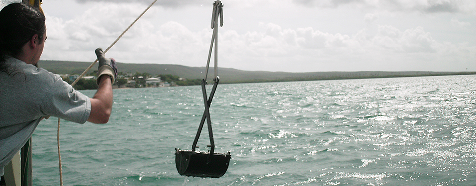 scientist collecting sediment samples from a boat in Guanica Bay, Puerto Rico