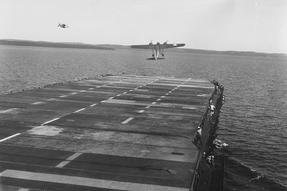 Launching a TDN-1 drone while steaming off Traverse City, Michigan, during flight tests on 10 August 1943. This plane has assumed an excessive nose-up attitude and is probably about to stall. Note the J2F amphibian flying off the ship's port bow, possibly acting as a drone control aircraft.