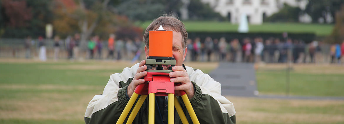 a geodesist on the National Mall looking through surveying device