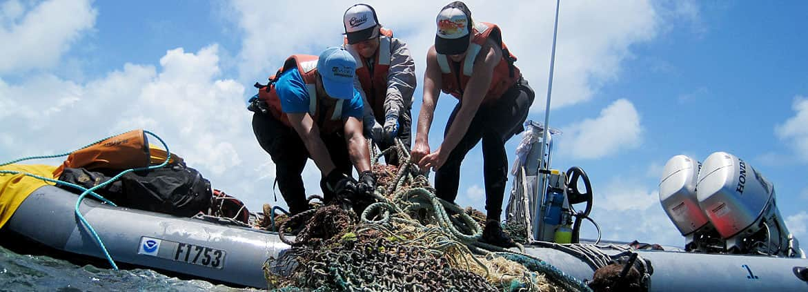 Scientists load onto a small boat marine debris collected at Midway Atoll in Papahanaumokuakea Marine National Monument.