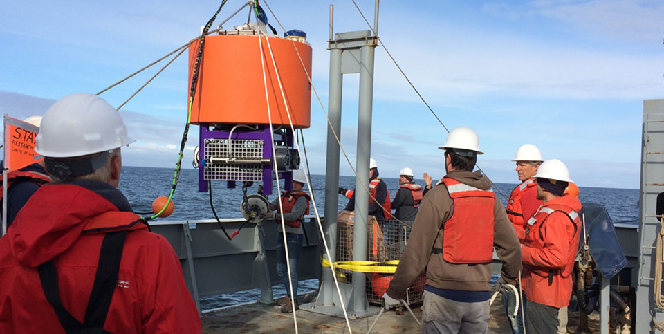 The Environmental Sample Processor (left) is an underwater robot that can remotely measure paralytic shellfish toxins. Here, the robot and a surface buoy with communication hardware (right) are readied for deployment in the Gulf of Maine. The sampling equipment for this tool is encased in a yellow steel housing to protect it from crushing ocean pressure. Credit: Woods Hole Oceanographic Institution