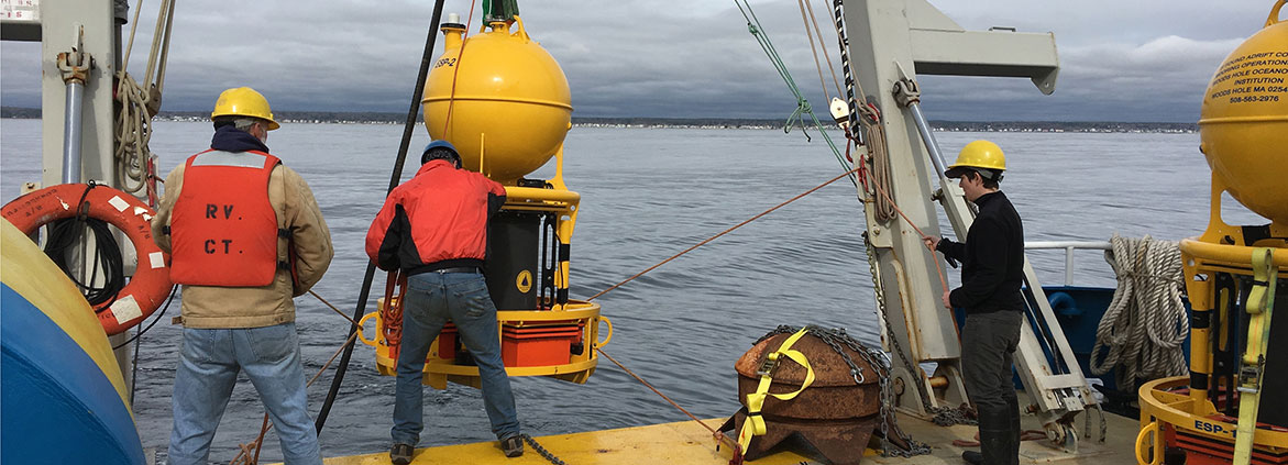 The Environmental Sample Processor (left) is an underwater robot that that can remotely measure paralytic shellfish toxins. Here, the robot and a surface buoy with communication hardware (right) are readied for deployment in the Gulf of Maine. The sampling equipment for this tool is encased in a yellow steel housing to protect it from crushing ocean pressure. Credit: Woods Hole Oceanographic Institution