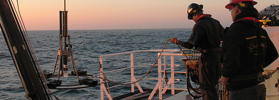 scientists guide sediment corer out of ocean