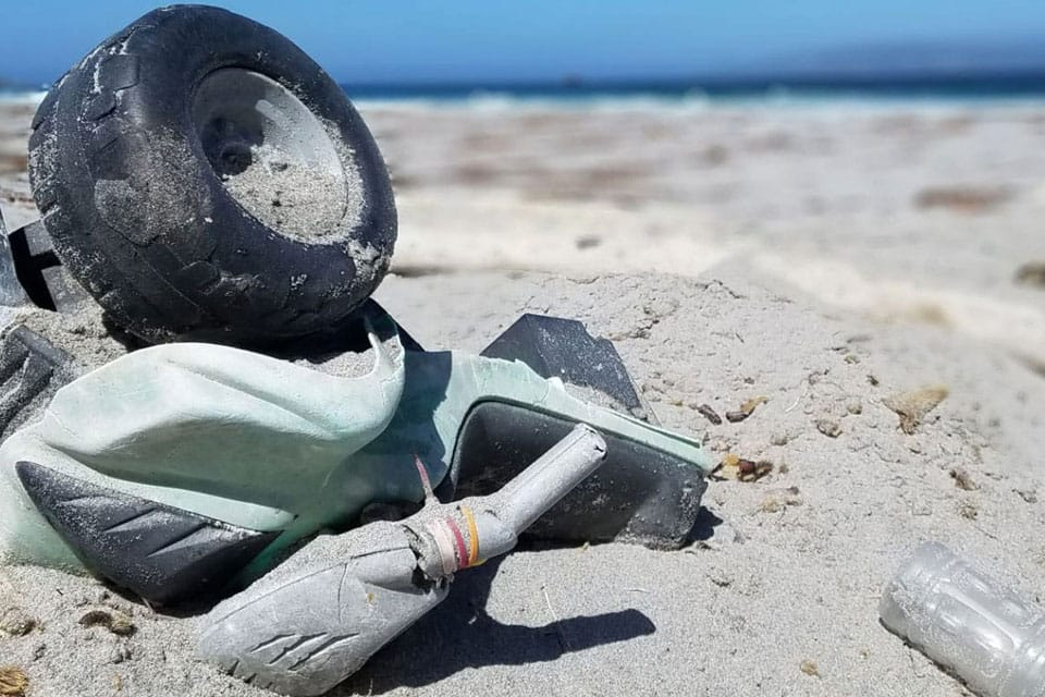 a toy truck buried in the sand at the beach
