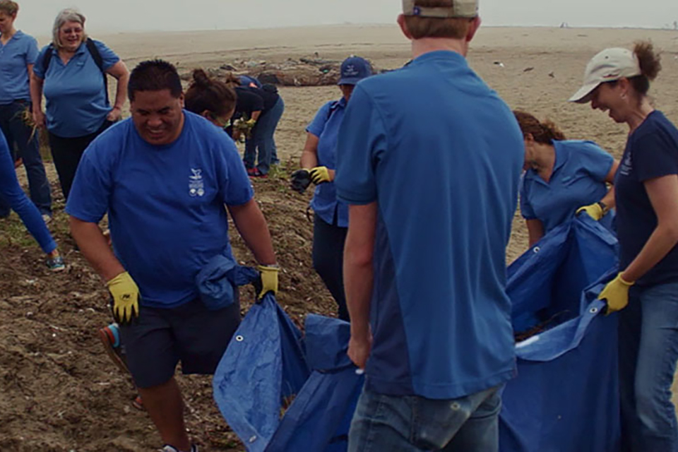 volunteers help clean up a beach
