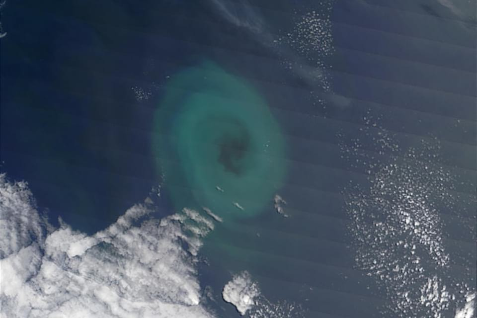 Photo of phytoplankton, which are microscopic marine organisms that use photosynthesis to create energy, that appear to be caught in a whirlpool, which causes them to swirl in a clockwise pattern.