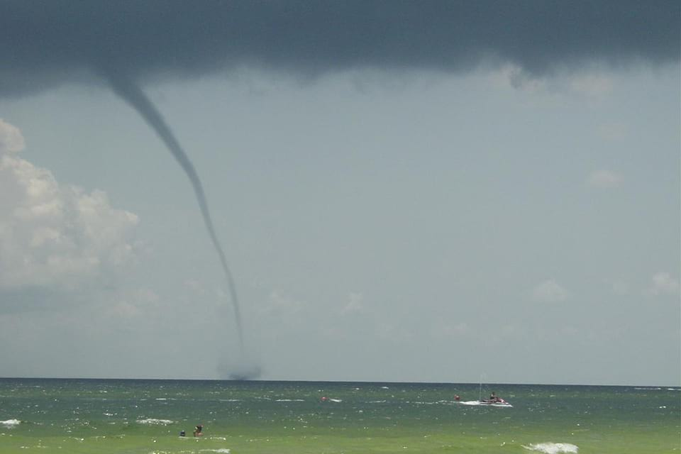 Photo of a waterspout close to a beach