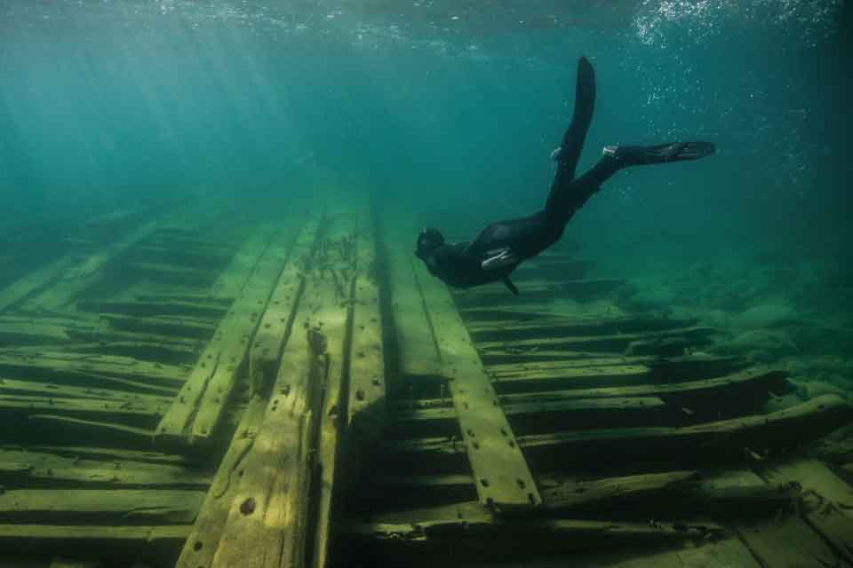 A snorkeler explores the shallow site of the sunken schooner Portland, lost in a Lake Huron storm in 1877. Credit: David Ruck.
