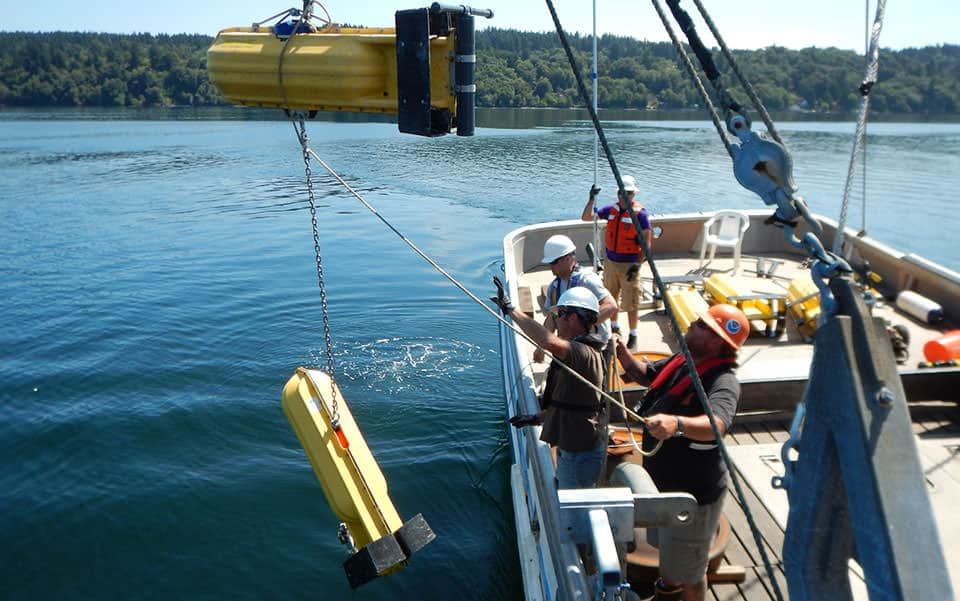 NOAA team deploys a current meter with surface floats.