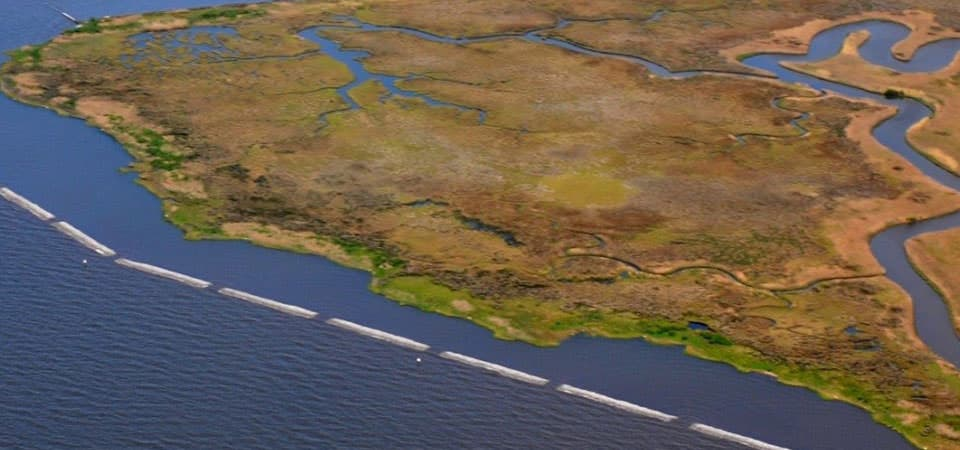 Aerial photo of the Mississippi coast with a living shoreline project that includes natural and artificial breakwater material and marsh creation to reduce shoreline erosion.
