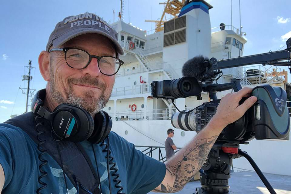 Kurt Mann holding a pro camera on the deck of the NOAA ship Ron Brown