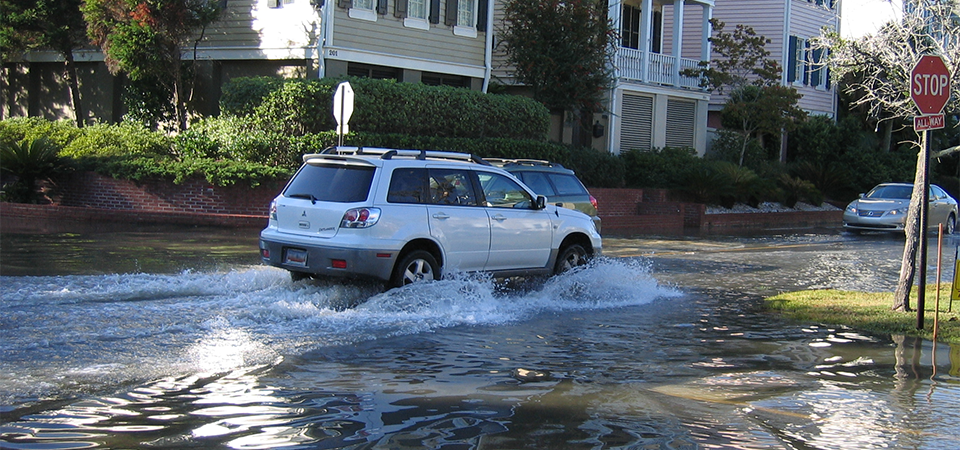 car drives on flooded street in Charleston, South Carolina