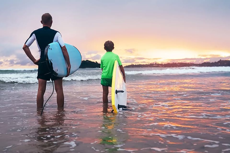 two surfers look out at the sun setting behind the oceans horizon