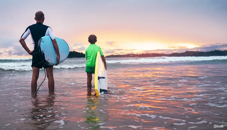 father and son about to surf on a beach